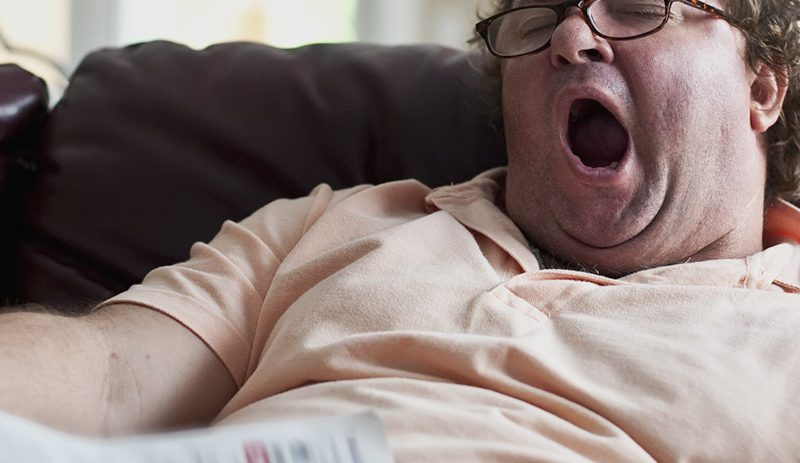 Lazy man yawning on couch